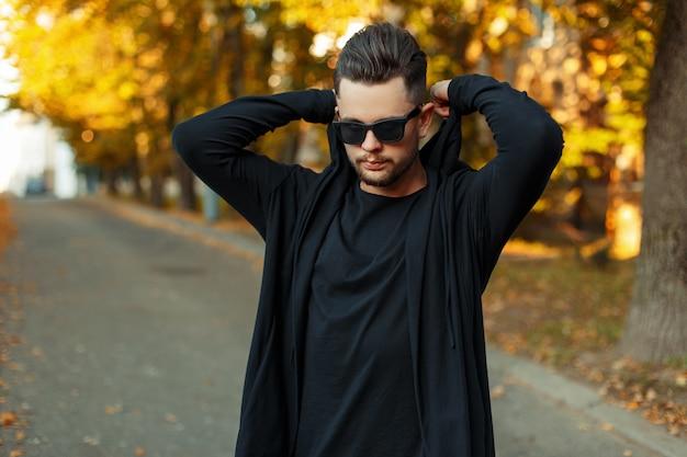 サングラスと黒いスウェットシャツのハンサムなスタイリッシュな男は、晴れた秋の日にフードをかぶる