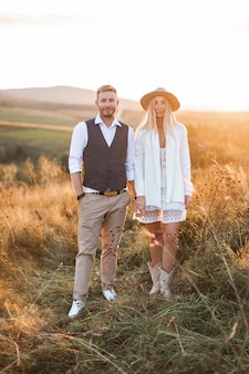Handsome stylish man in shirt, vest and pants and pretty boho woman in dress, jacket and hat walking in the field with straw bales