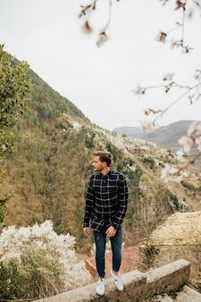 丘の上に立って春の花を楽しむハンサムなスタイリッシュな男。