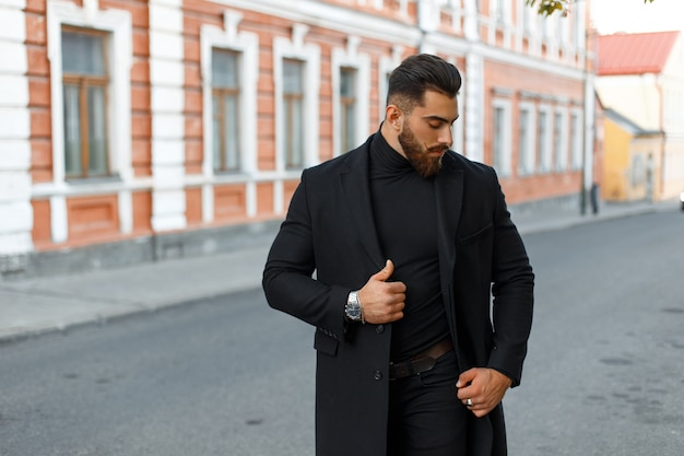 Handsome stylish strong man in a black trendy coat walks on the street