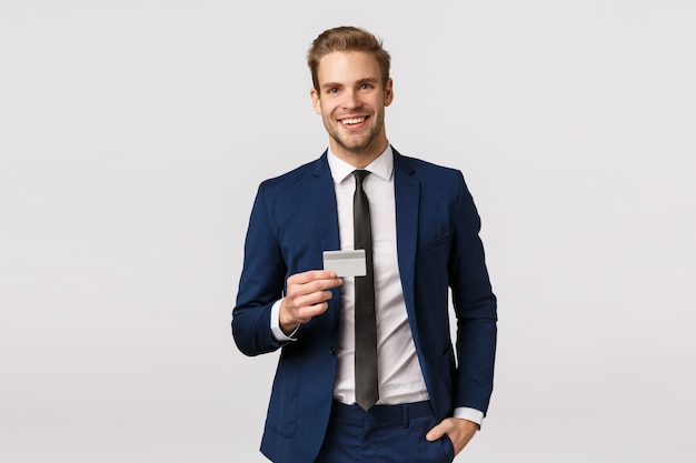 Handsome stylish successful blond businessman in classic suit, holding credit card and smiling self-assured, hand in pocket pants, promote banking system, make purchase, standing white background