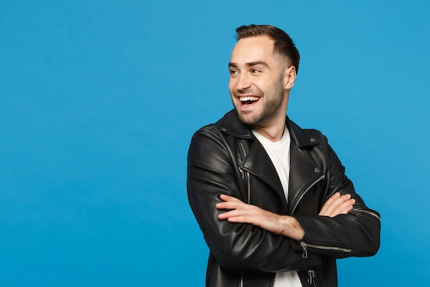 Handsome stylish young bearded man in black leather jacket white t-shirt looking aside isolated on blue wall background studio portrait. people sincere emotions lifestyle concept. mock up copy space.