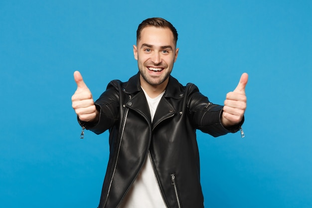 Handsome stylish young bearded man in black leather jacket white t-shirt looking camera isolated on blue wall background studio portrait. people sincere emotions lifestyle concept. mock up copy space.