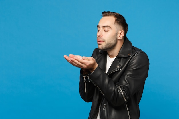 Handsome stylish young bearded man in black leather jacket white t-shirt send air kiss isolated on blue wall background studio portrait. people sincere emotions lifestyle concept. mock up copy space.