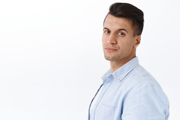 Handsome stylish young caucasian, masculine man turn face and look with pleased confident smile, concept of safety, insurance and people. adult guy standing over white wall