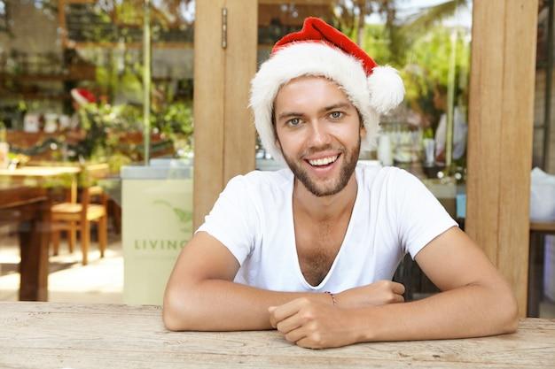 サンタクロースの格好をして、カメラに向かって幸せそうに笑って、企業のパーティーで新年を祝っている間楽しんでいるハンサムなスタイリッシュな若者。