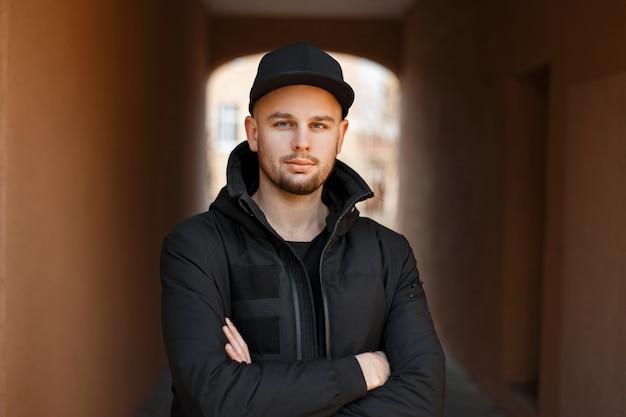 검은 야구 모자와 겨울 패션 재킷에 잘 생긴 세련된 젊은 힙 스터 남자가 서 있고 거리에서 카메라를 쳐다 본다.