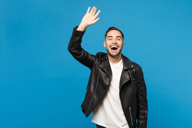 Handsome stylish young man in black jacket white t-shirt waving and greeting with hand as notices someone isolated on blue wall background studio portrait. people lifestyle concept. mock up copy space