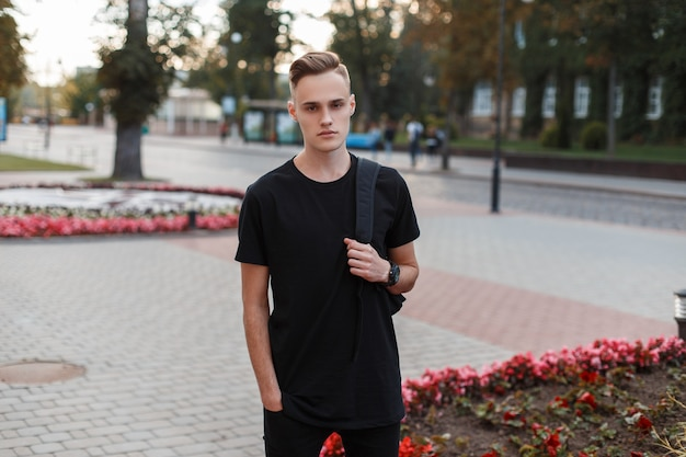 ジーンズのスタイリッシュな髪型のスタイリッシュなバックパックとファッショナブルな黒のtシャツを着たハンサムでスタイリッシュな若い男は、暖かい夏の日に街を旅します。