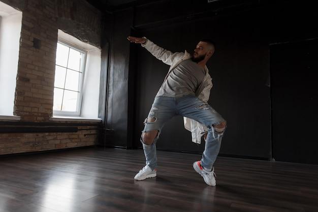 세련된 흰색 재킷과 세련된 찢어진 청바지에 잘 생긴 세련된 젊은 남자가 어두운 벽에 춤을