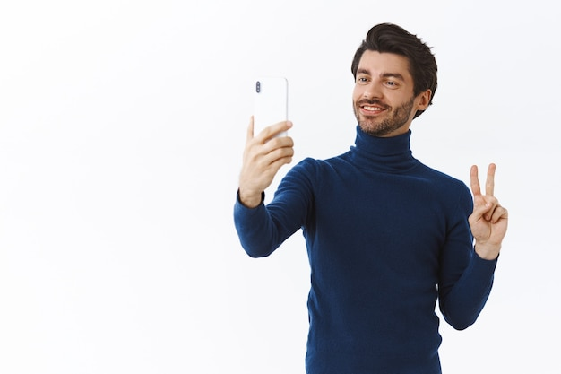 Красивый стильный молодой человек в модном свитере с высоким воротом на рождественскую вечеринку, делает селфи для публикации в интернете, держит смартфон, делает жест мира и мило улыбается, белая стена