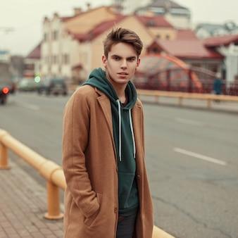 거리에 까마귀와 트렌디 한 복고풍 코트에 잘 생긴 세련된 젊은 남자