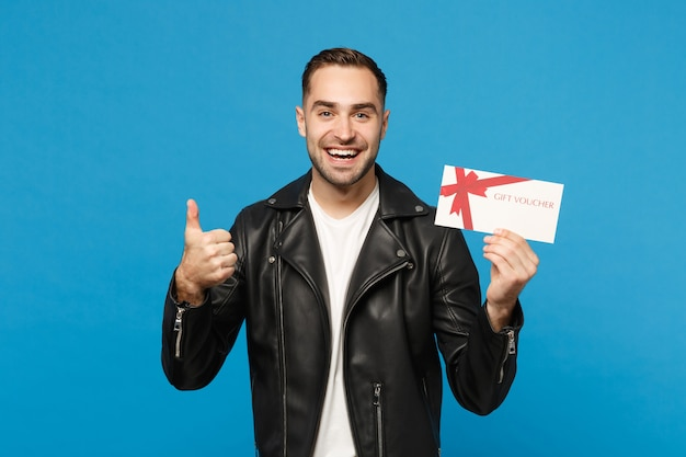 Handsome stylish young unshaven man in black jacket white t-shirt hold gift certificate isolated on blue wall background studio portrait. people sincere emotions lifestyle concept. mock up copy space.