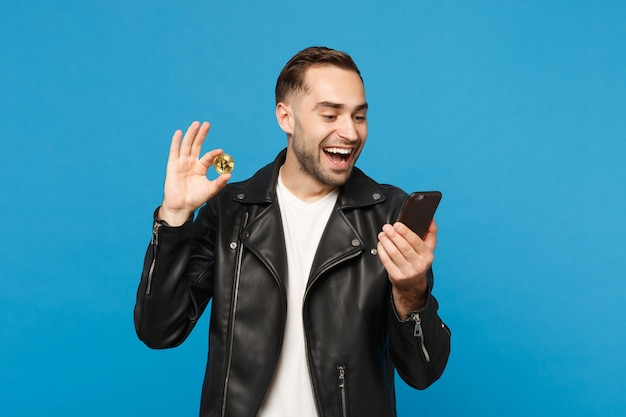 Handsome stylish young unshaven man in black jacket white t-shirt hold in hand cellphone bitcoin currency isolated on blue wall background studio portrait. people lifestyle concept. mock up copy space