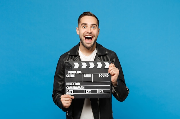 Handsome stylish young unshaven man in black jacket white t-shirt hold in hand film making clapperboard isolated on blue wall background studio portrait. people lifestyle concept. mock up copy space.