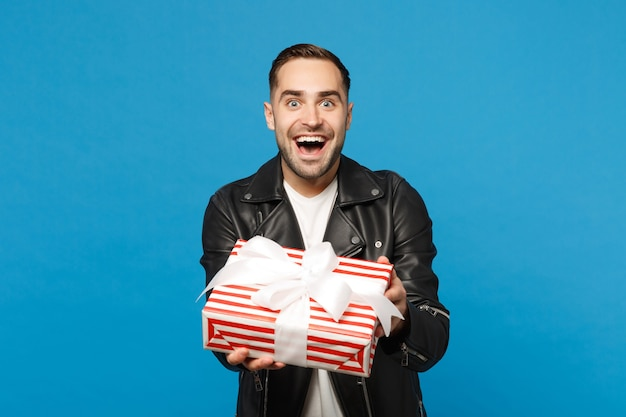 Handsome stylish young unshaven man in black leather jacket white t-shirt hold gift box isolated on blue wall background studio portrait. people sincere emotions lifestyle concept. mock up copy space.