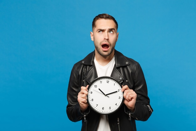 Handsome stylish young unshaven man in black leather jacket white t-shirt holding round clock isolated on blue wall background studio portrait. people lifestyle concept. hurry up. mock up copy space.