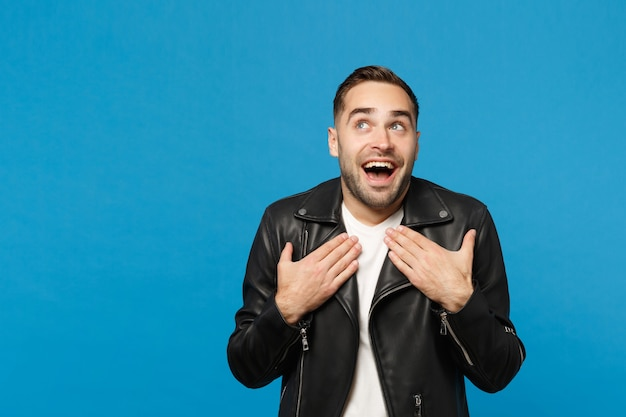 Handsome stylish young unshaven man in black leather jacket white t-shirt looking camera isolated on blue wall background studio portrait. people sincere emotions lifestyle concept. mock up copy space