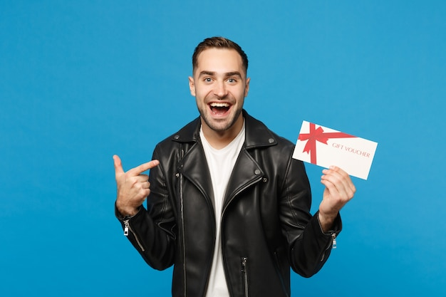 Красивый стильный молодой небритый мужчина в черной куртке белой футболке держит подарочный сертификат на синем стенном фоне студийного портрета. концепция образа жизни искренние эмоции людей. копируйте пространство для копирования.