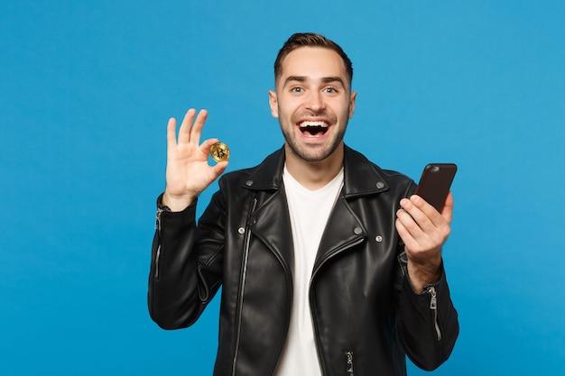 Красивый стильный молодой небритый мужчина в черной куртке белой футболке держит в руке биткойн сотового телефона, изолированную на синем стенном фоне студийного портрета. концепция образа жизни людей. копировать пространство для копирования