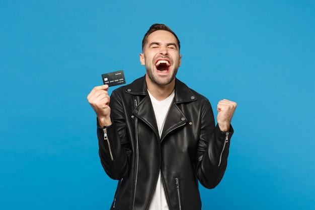 Красивый стильный молодой небритый мужчина в черной кожаной куртке белой футболке держит в руке кредитную банковскую карту, изолированную на синем стенном фоне студийного портрета. концепция образа жизни людей. копируйте пространство для копирования.