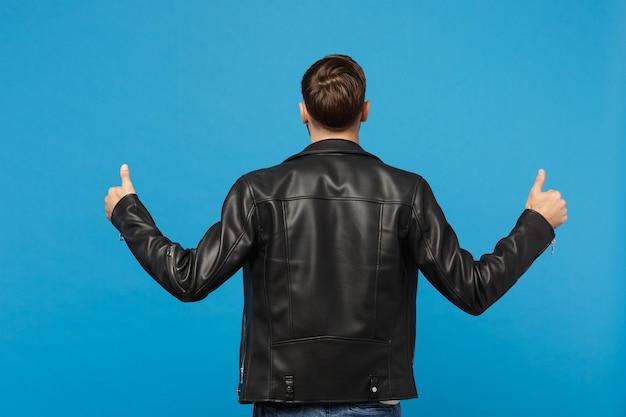 파란색 배경 스튜디오 초상화에 격리된 검은색 가죽 재킷 흰색 티셔츠를 입은 잘생긴 세련된 젊은 남자. 사람들은 진심 어린 감정 라이프 스타일 개념입니다. 모의 복사 공간