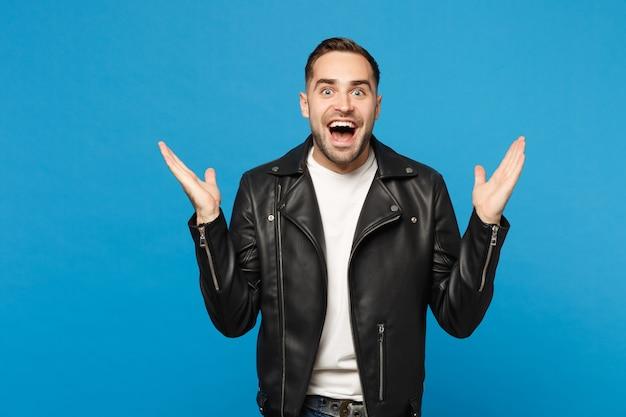 青い壁の背景スタジオの肖像画に分離されたカメラを探している黒い革のジャケット白いtシャツのハンサムなスタイリッシュな若い無精ひげを生やした男。人々の誠実な感情のライフスタイルの概念。コピースペースのモックアップ