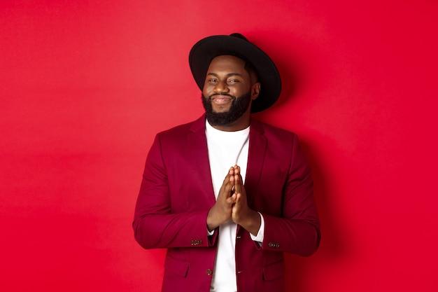 Un bell'uomo di colore di successo assapora il profitto, si sfrega le mani e sorride soddisfatto, in piedi su sfondo rosso in abito da festa