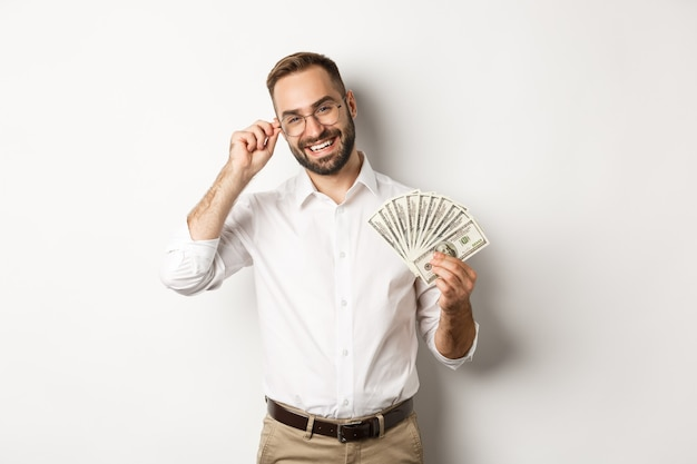 Handsome successful businessman holding money, fixing glasses on nose, standing over white background.