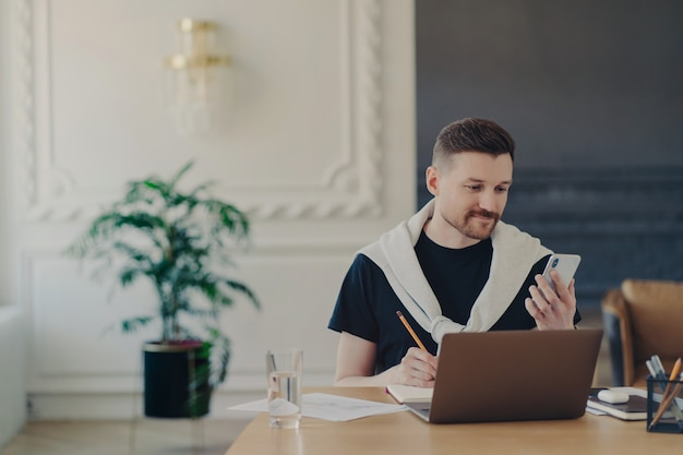 스마트폰을 사용하여 평상복을 입은 잘생긴 성공적인 사업가, 노트북에 중요한 연락처를 작성하거나 소셜 미디어에서 비즈니스 웹 세미나를 시청합니다. 홈 오피스에서 노트북 작업을 하는 남성 프리랜서
