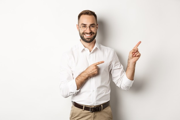 Handsome successful businessman pointing fingers right, showing advertisement with pleased face, white background.