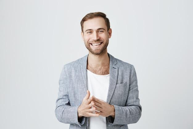 ハンサムな成功した実業家の手をこすりと笑顔