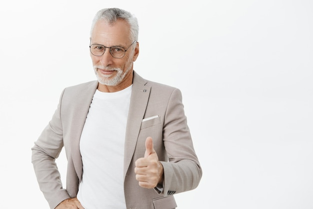 Handsome successful senior businessman showing thumbs-up in approval