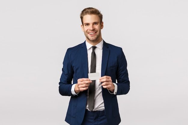 Handsome, successful young businessman in classic blue suit, holding credit card and smiling joyfully