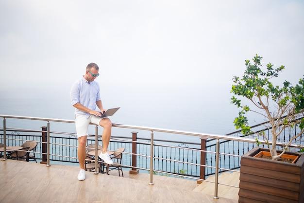 Красивый успешный молодой мужской бизнесмен, работающий с ноутбуком, смотрит на средиземное море. на нем рубашка и белые шорты. удаленная работа в отпуске. концепция отпуска