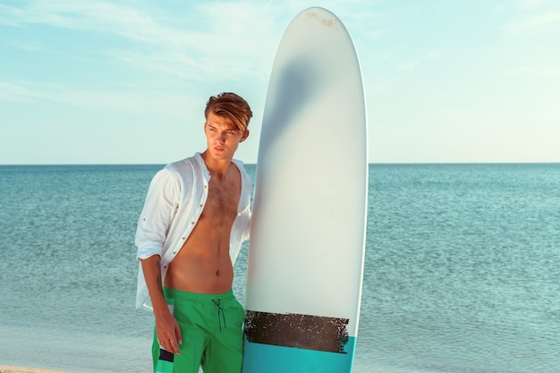Handsome surfer holding his surfboard