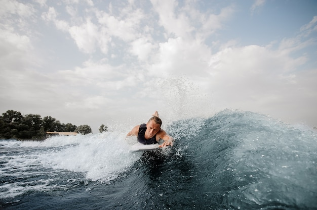 Handsome surfer lying on white board and swimming down the river