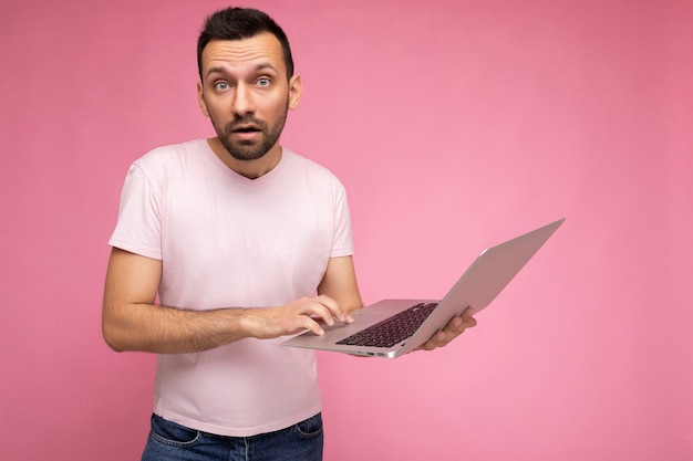 Handsome surprised and amazed man holding laptop computer looking at camera and typing on the keyboard in t-shirt
