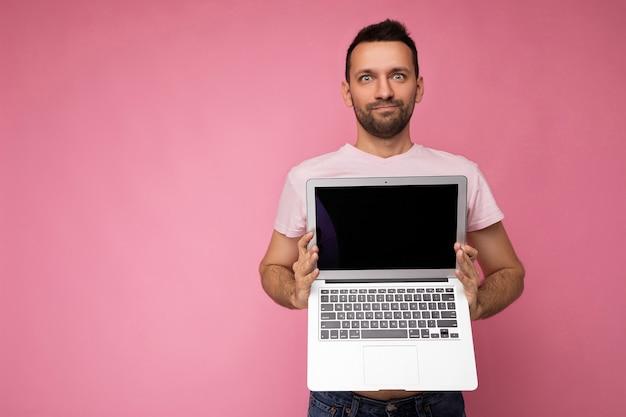 Красивый удивленный мужчина держит портативный компьютер, глядя в камеру в футболке на изолированном розовом
