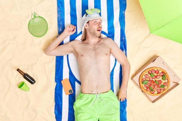 Красивый удивленный рыжий мужчина в шляпе и шортах проводит свободное время на пляже, ест вкусную пиццу, пьет пиво, ленивый день проводит летние каникулы на берегу моря. люди и концепция отдыха