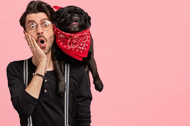 Il giovane designer maschio con la barba lunga sorpreso bello tiene il cane nero sulla spalla, tiene la mano sulla guancia, dimentica qualcosa, sta contro il muro rosa con lo spazio della copia. concetto di amicizia