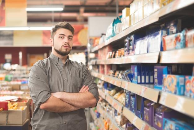 スーパーでメモリストと立っているハンサムなスウェーデン人の顧客