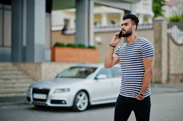 Handsome tall arabian beard man model at stripped shirt posed outdoor against car.