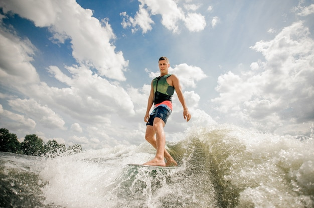 Handsome tall man wakesurfing on the board down the river against the cloudy sky and trees