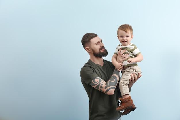 귀여운 어린 소년을 들고 잘 생긴 문신 된 젊은 남자