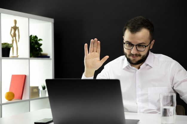 Handsome teacher holds video conference on laptop, raised hand in greeting
