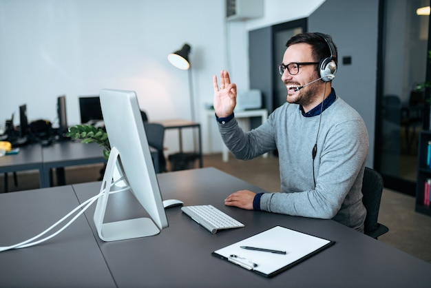 Handsome technical support agent talking to a client and giving him okay sign. video call.
