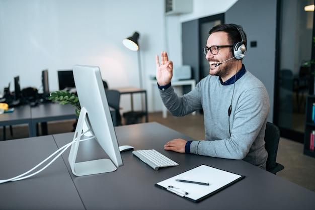 잘 생긴 기술 지원 요원이 고객과 대화하고 괜찮은 서명을합니다. 영상 통화.