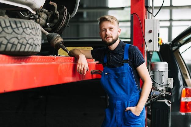 Красивый техник в автомобильной мастерской