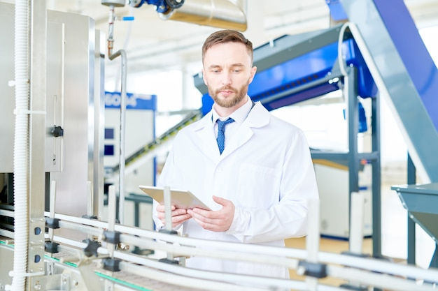 Handsome technologist controlling production process